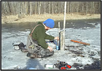 Installing water-level and water-temperature loggers in a Minnesota wetland. Courtesy of the U.S. Fish and Wildlife Service.